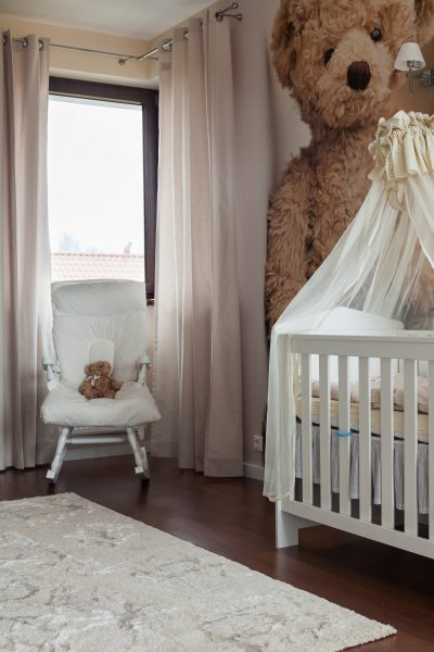 Photo of cute toddler room with white cradle